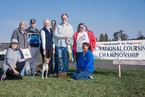Chief poses with his tribe and American Kennel Club National Lure Coursing officials following his triumph. He is the first basenji to win the title.