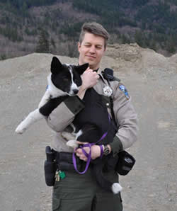 Following the pursuit and successful apprehension of a bear, Officer Nick Jorg holds his Karelian Bear Dog Colter.