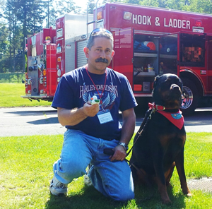 """Steve Berko and his 5-year-old Rottweiler Dascha, were popular regulars at Reed Intermediate School following the shootings. Berko's family were neighbors to the shooter, Adam Lanza's, family. """"I've seen the worst in humanity but the best in a community coming together,"""" he said."""